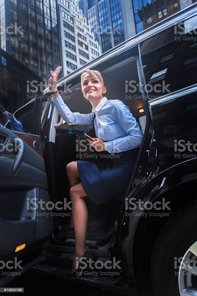 Young smiling woman getting out of car stock photo