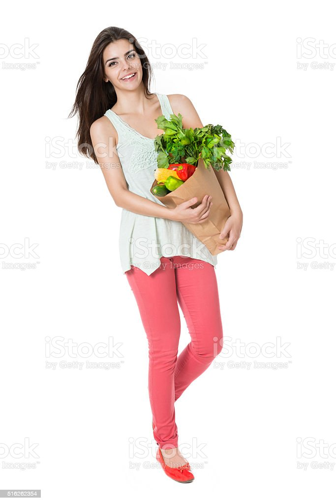 Young Smiling Woman Holding a Bag Full of Groceries stock photo
