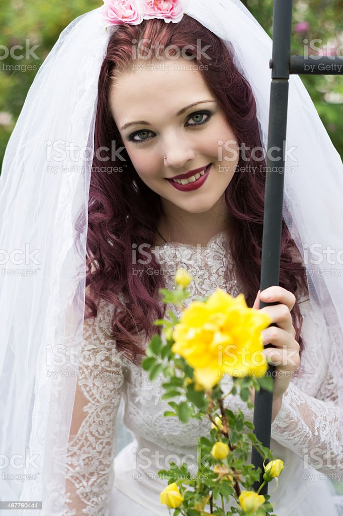 Young smiling woman in wedding dress with Persian Yellow rose. stock photo