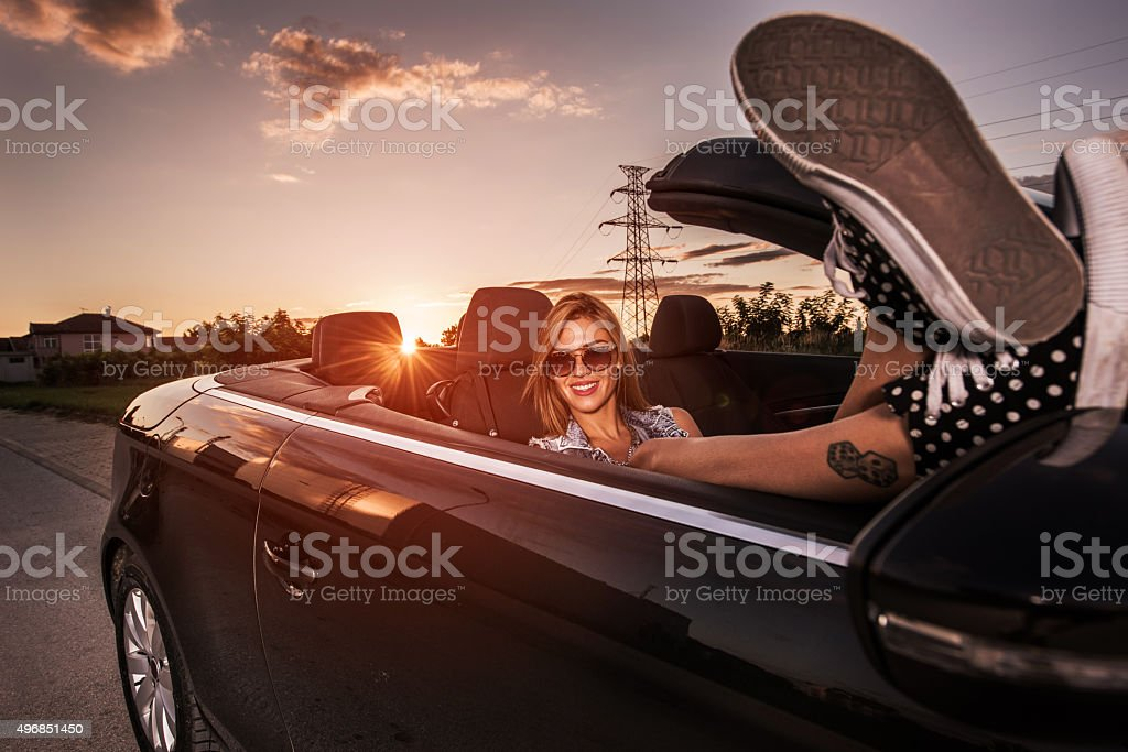 Young smiling woman relaxing in convertible car at sunset. stock photo