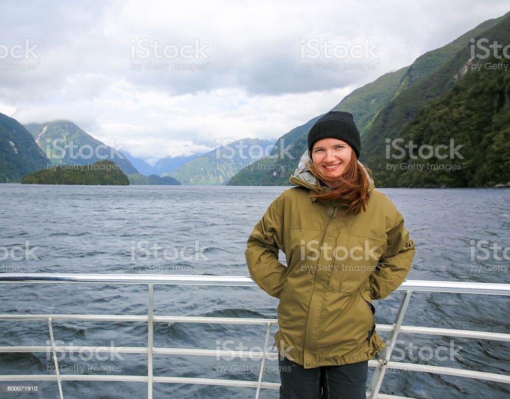 Young smiling woman  standing on the boat deck. NZ stock photo