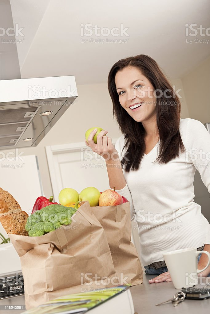 Young smiling woman with groceries in the kitchen royalty-free stock photo