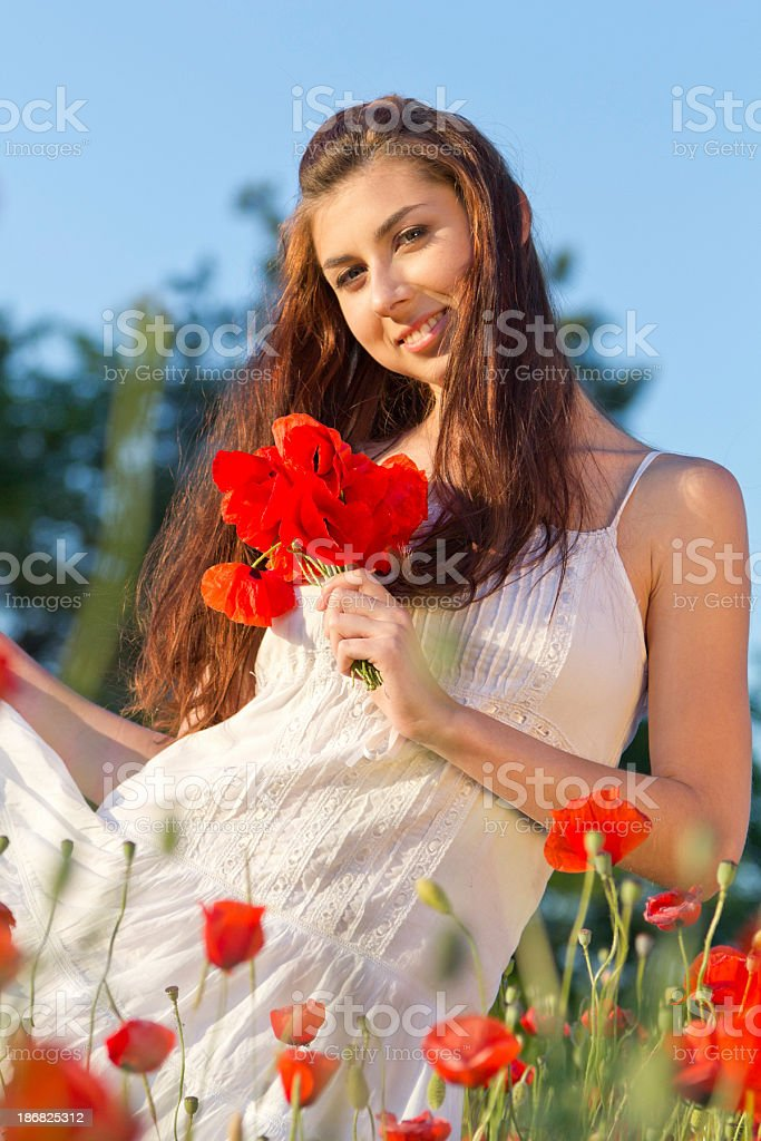 Young smiling woman with red poppies bouquet on meadow royalty-free stock photo