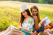 Young smiling women relaxing in nature and studying