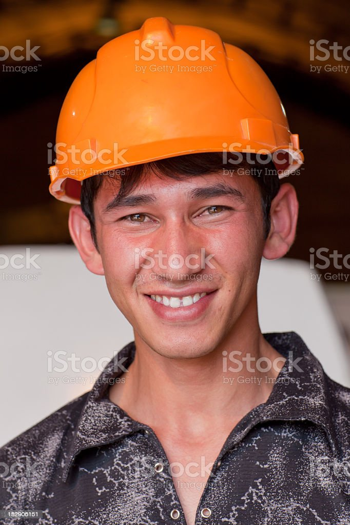 Young Smiling Worker in front of workshop stock photo