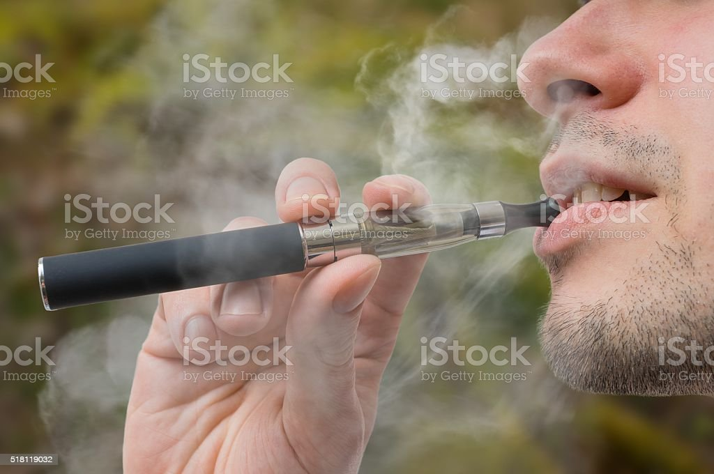 Young smoker is vaping e-cigarette or vaporizer. stock photo