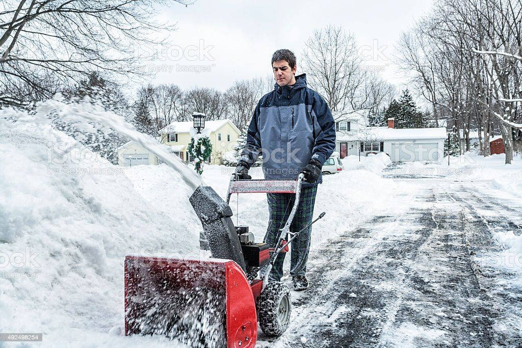 Young Snowblower Guy Clearing Snow From Suburban Driveway stock photo