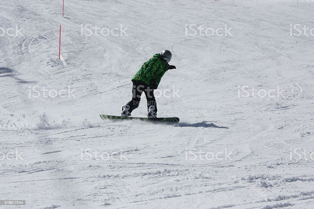 Young snowboard man sliding downhill. stock photo