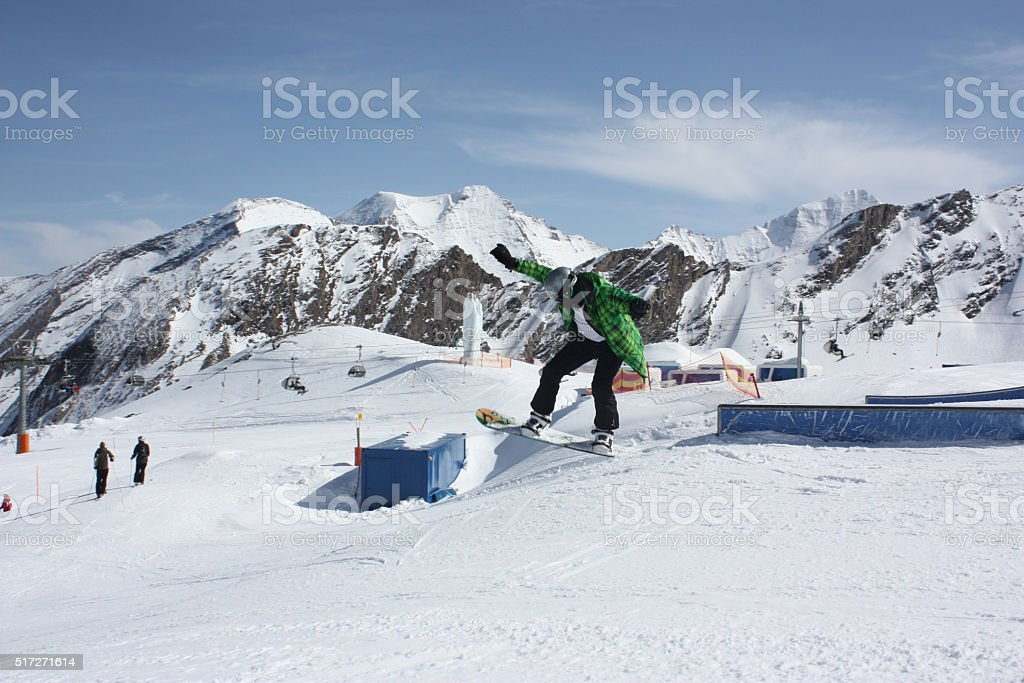Young snowboarder man sliding on a box. stock photo
