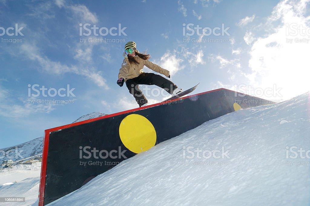 young snowboarder woman jibbing stock photo