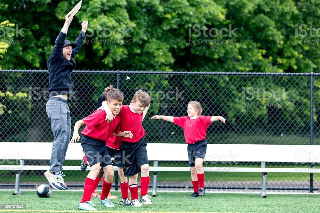 Young soccer coach celebrates with his team stock photo