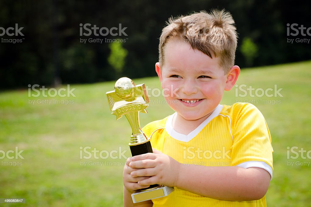 Young soccer player in uniform admiring his new trophy stock photo