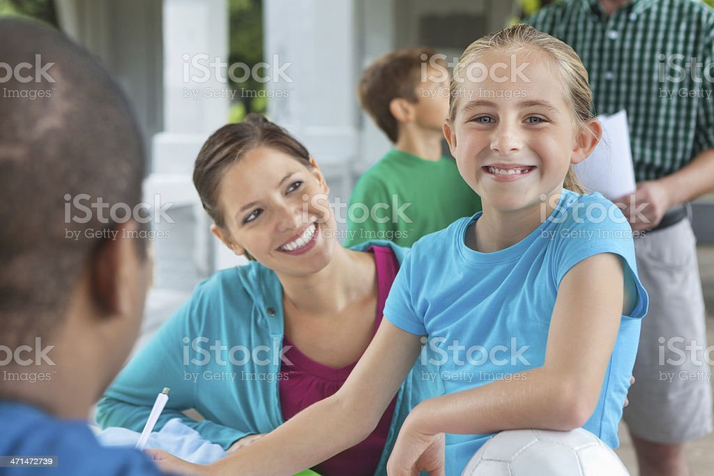 Young soccer star signing up for sports team with mom stock photo