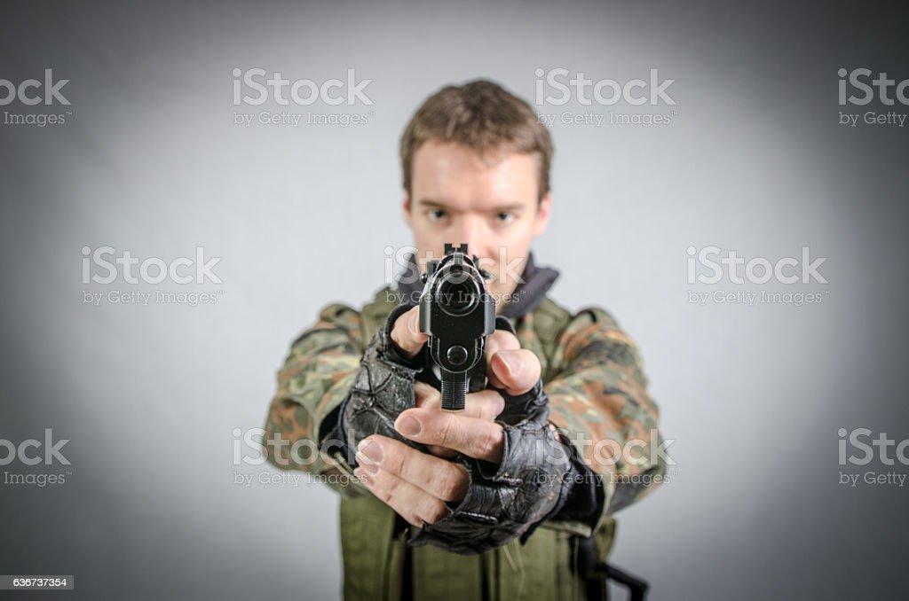Young soldier aiming a gun at camera stock photo