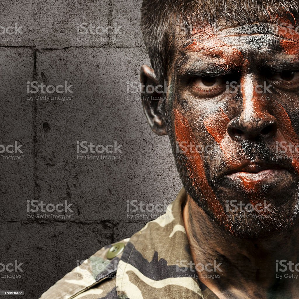 young soldier with camouflage paint looking very serious against stock photo