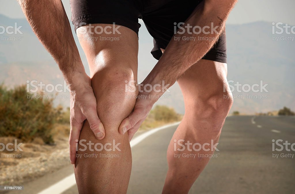 young sport man holding knee in pain suffering muscle injury stock photo