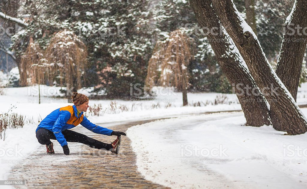Young sport woman doing exercises during winter training outside in stock photo