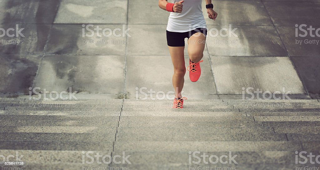 young sport woman running upstairs on city stairs stock photo