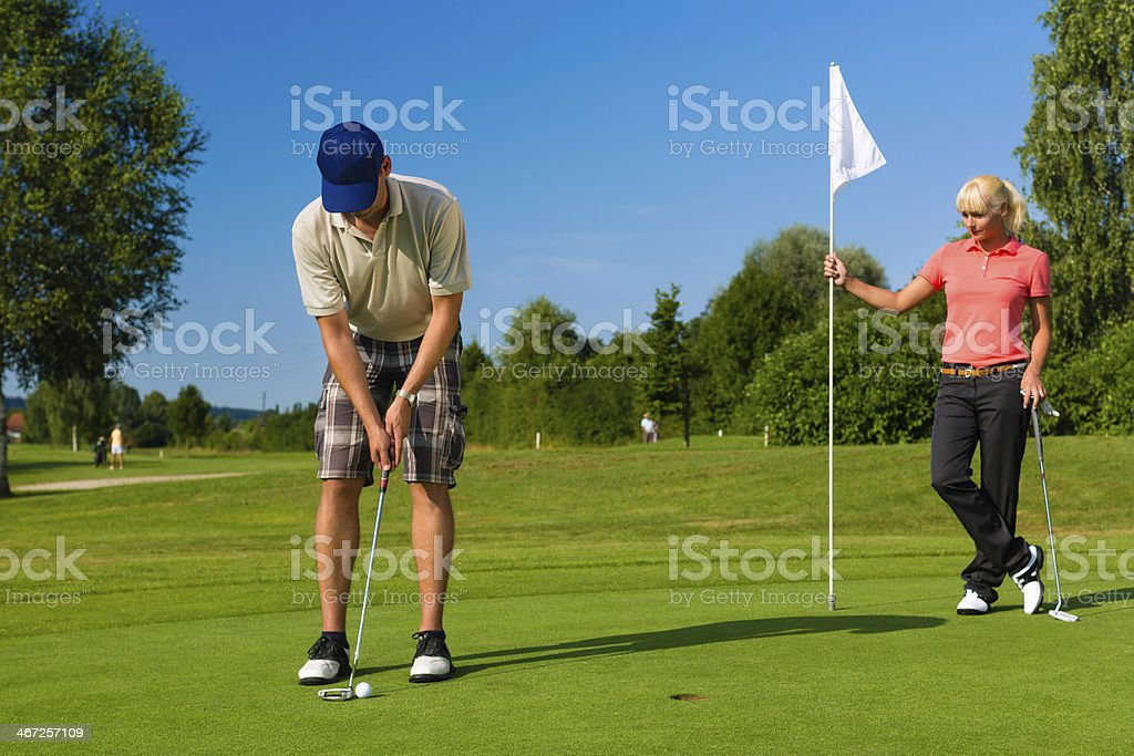 Young sportive couple playing golf on a course stock photo