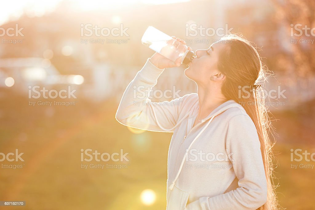 young sportive woman drinking water at sunset stock photo