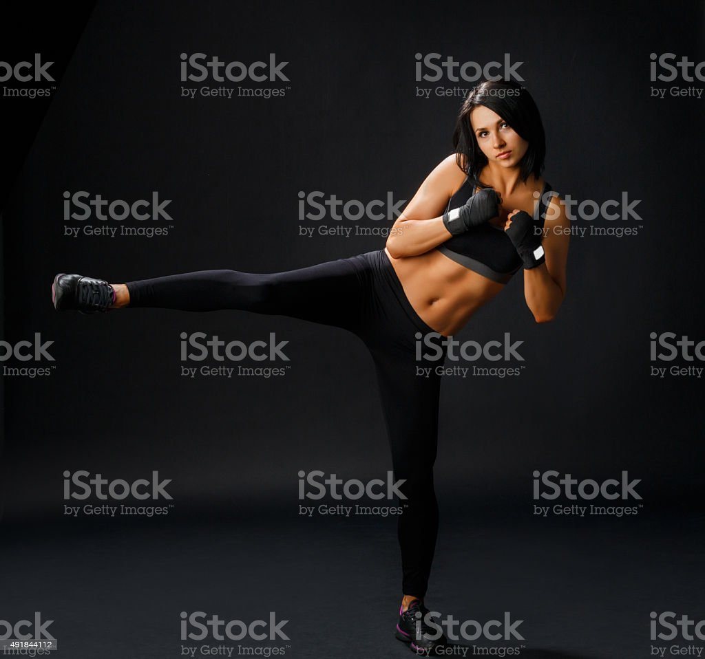 Young sportive woman makes tae bo side leg kick stock photo