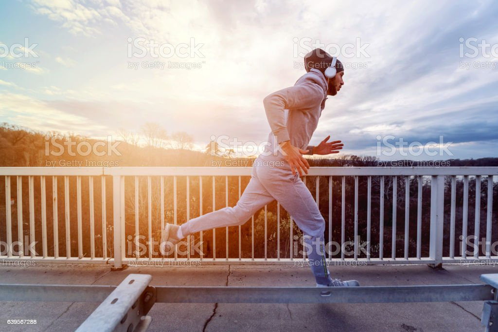 Young sports man with earphones running along road stock photo