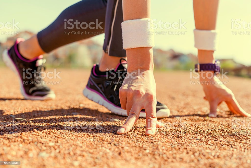 Young sports woman in start position preparing to run. stock photo