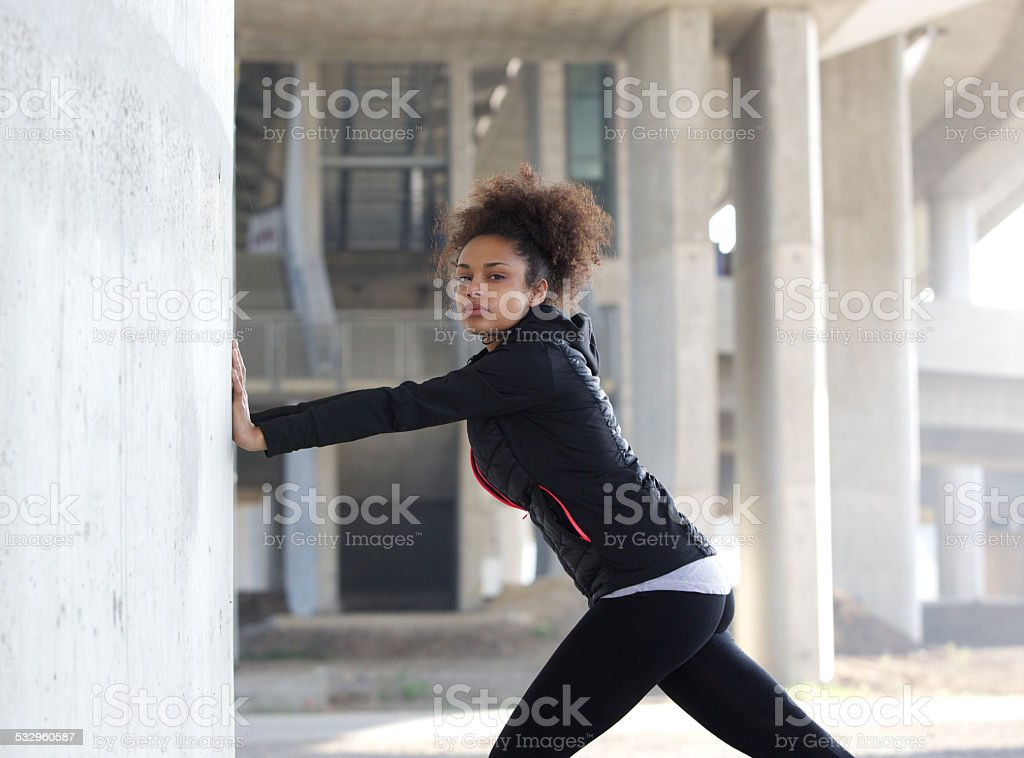 Young sports woman pushing against wall stock photo