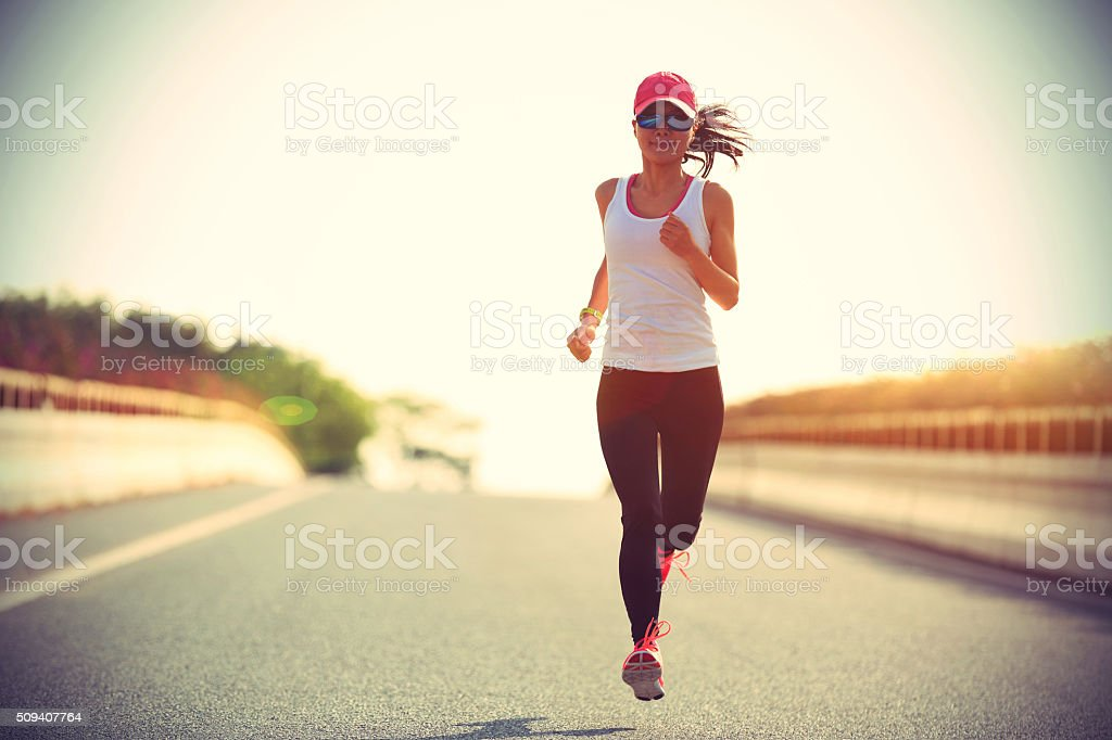 young sports woman runner running on city road stock photo