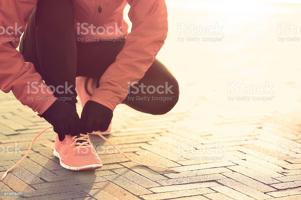 young sports woman runner tying shoelace at sunrise stock photo