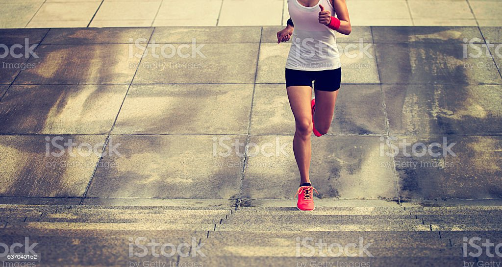 young sports woman running upstairs on city stairs stock photo