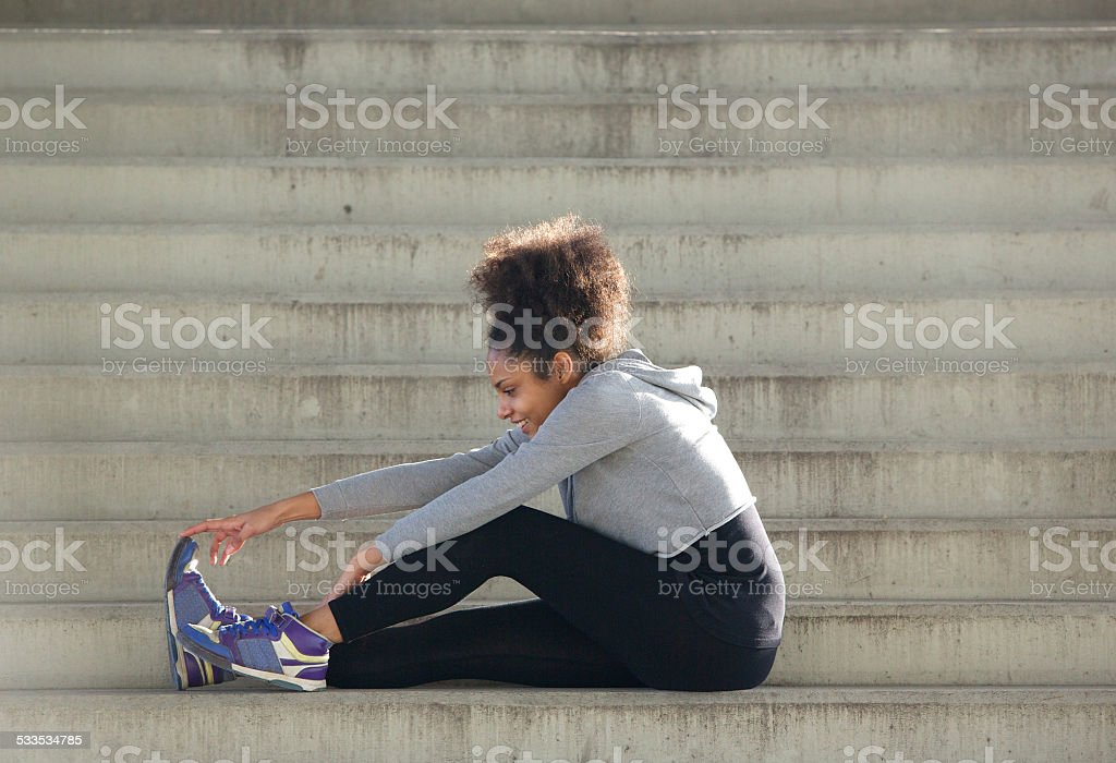 Young sports woman sitting on stairs stretching leg muscles stock photo