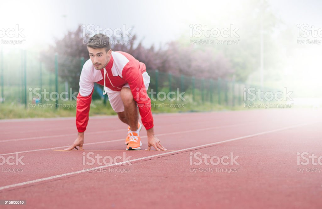 Young sportsman in low start ready to sprint stock photo