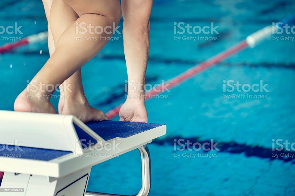 Young sportsman on a swimming starting block stock photo