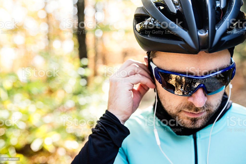 Young sportsman riding bicycle outside in sunny autumn nature stock photo