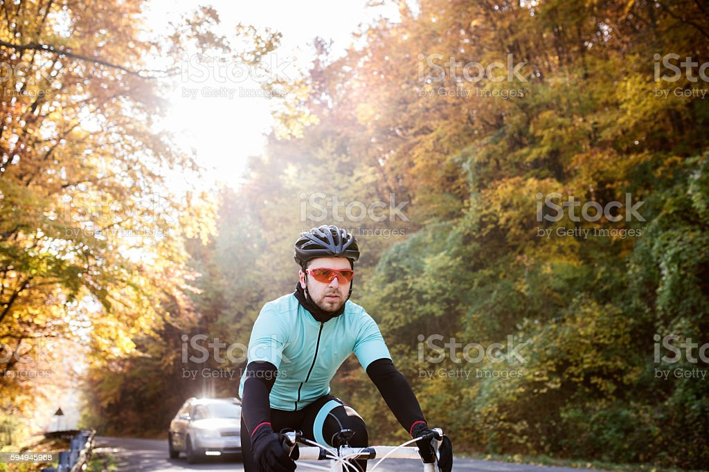 Young sportsman riding his bicycle outside in sunny autumn natur stock photo