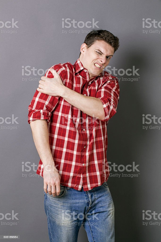 young sportsman shouting from muscle cramp in his arm stock photo