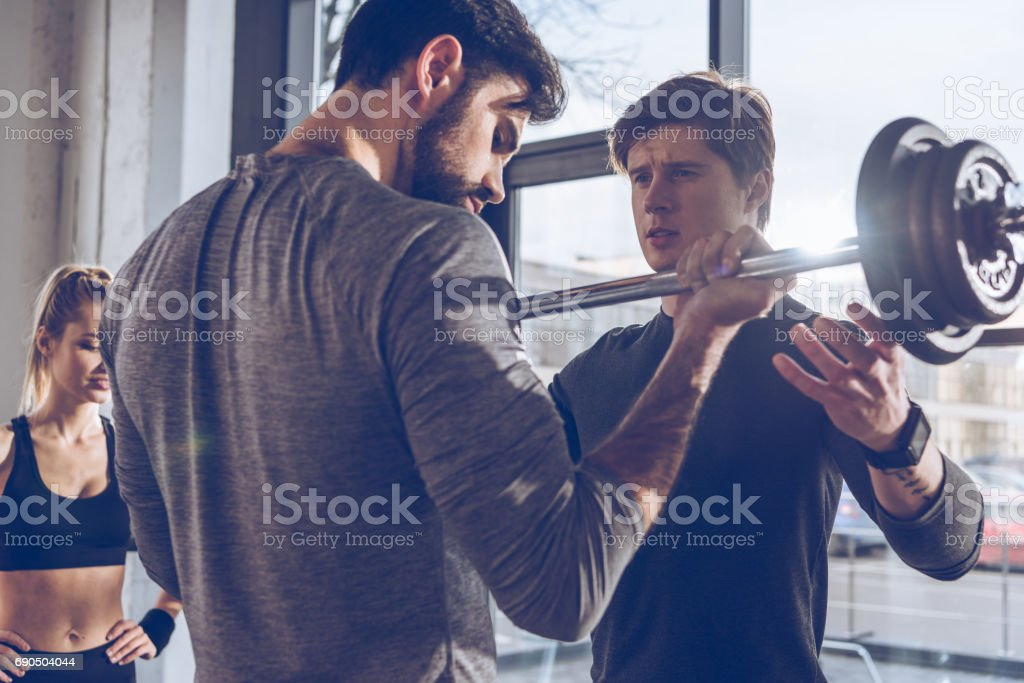 Young sportsmen exercising with barbell and sportswoman standing behind at gym workout stock photo