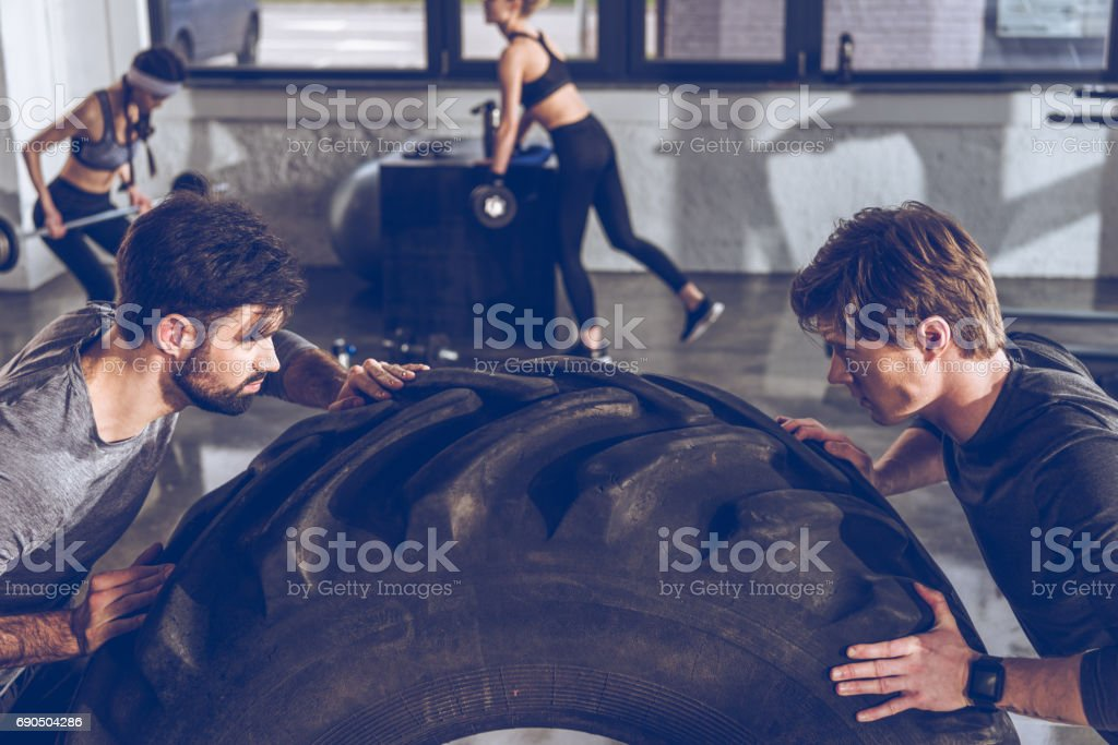 Young sportsmen exercising with big tire at gym workout stock photo