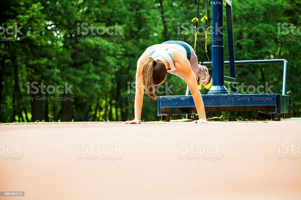 Young sportswoman doing push-ups in nature stock photo