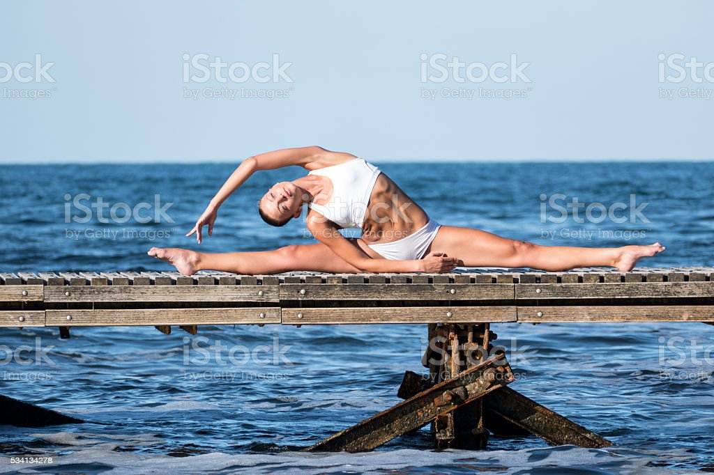 Young sportswoman exercising on a pier stock photo