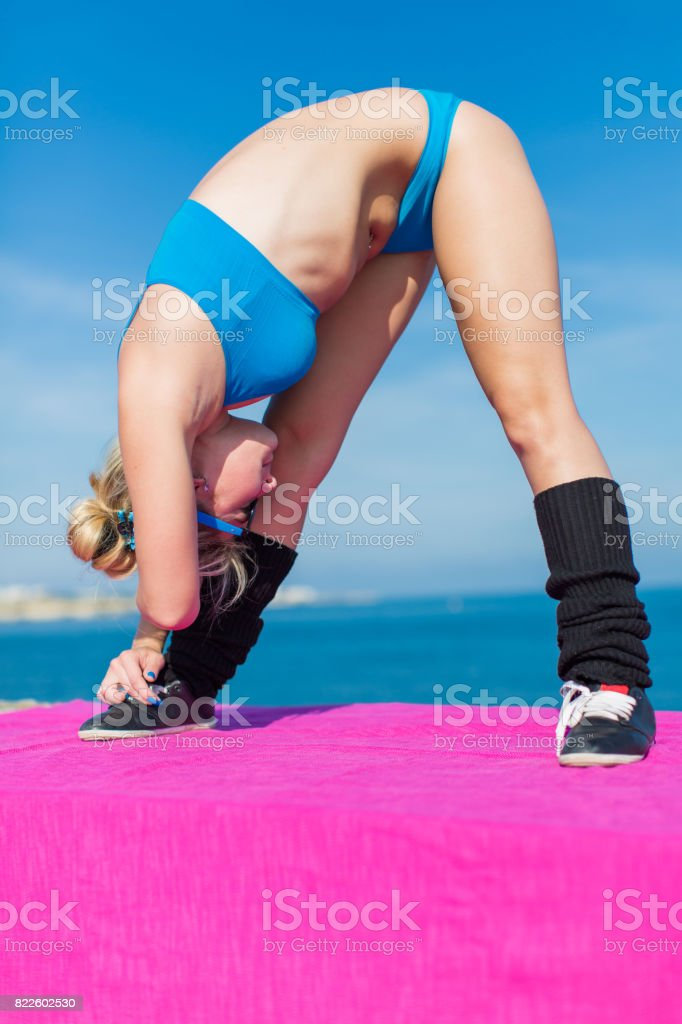 Young sportswoman in blue sportswear doing exercises outdoors stock photo
