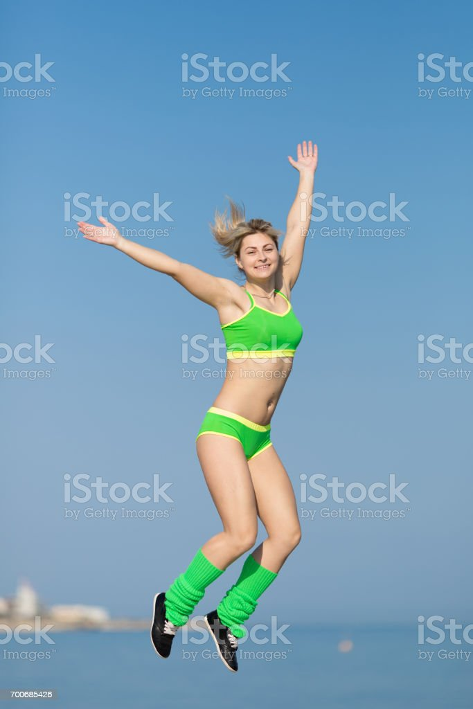 Young sportswoman in green sportswear and sunglasses jumping with hands raised stock photo