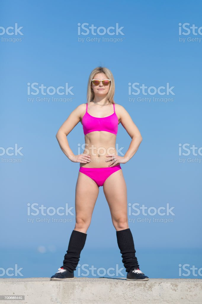 Young sportswoman in sunglasses doing exercises on concrete wall stock photo