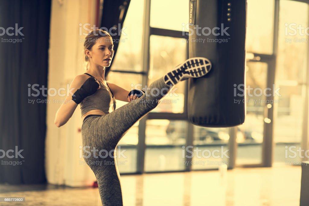 young sportswoman kicking punching bag in sports center