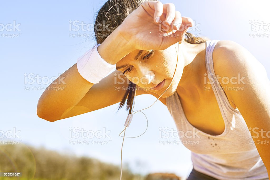 Young sportswoman resting after running. stock photo