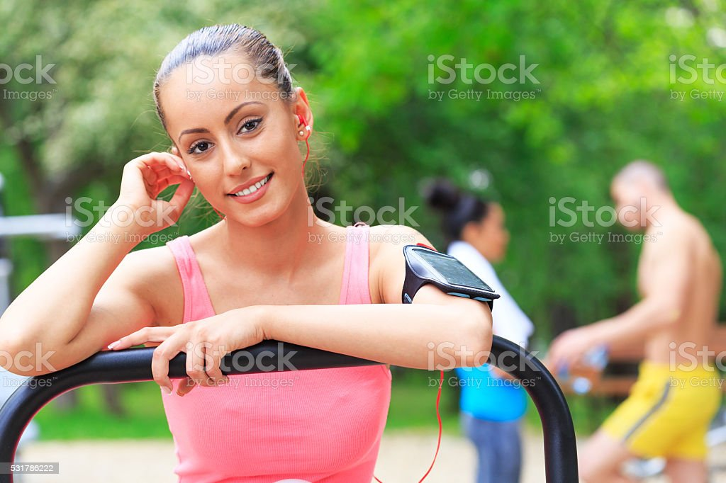 Young sportswoman resting on air walker in the park stock photo