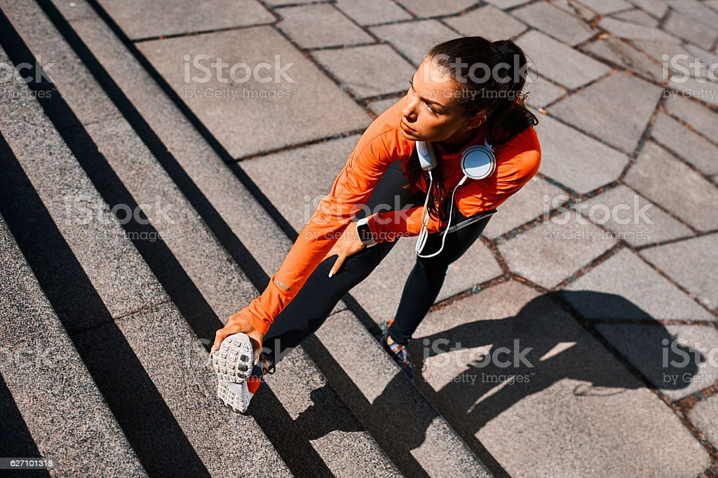 Young sportswoman stretching after cardio session stock photo