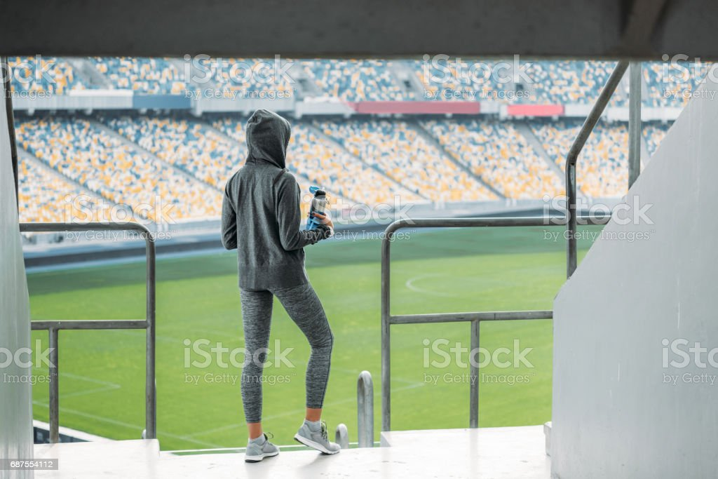 young sportswoman with sport bottle standing at handrail on stadium stock photo