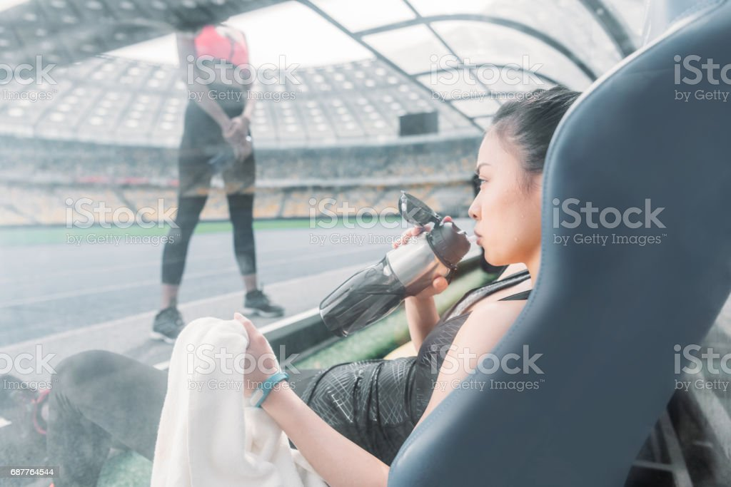Young sportswoman with towel and bottle sitting on stadium seat and looking at sporty girl stock photo